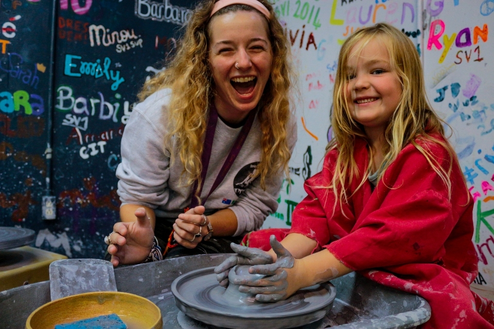 Counselor teaches pottery to a young girl at Family Camp
