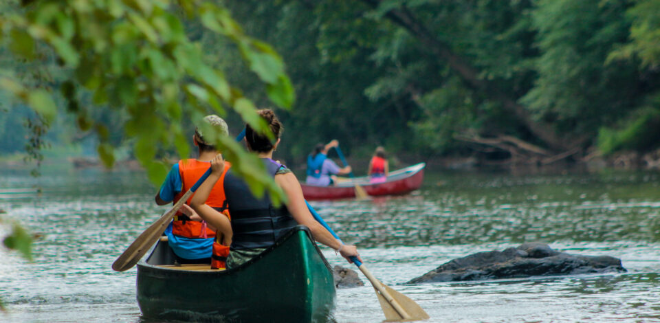 Teen campers canoe down a local Virginia river adjacent to camp.