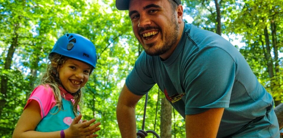 Counselor and camper get ready for the High Ropes activity at a sleep-away camp in Virginia
