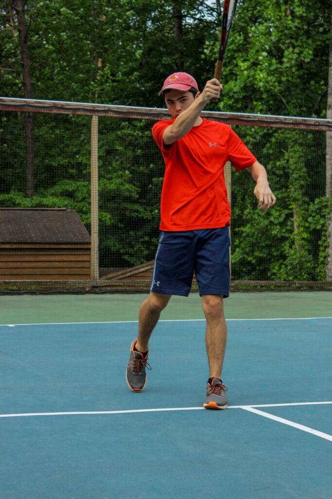 Senior village boy swings his racket at Camp Friendship summer tennis camp in Virginia