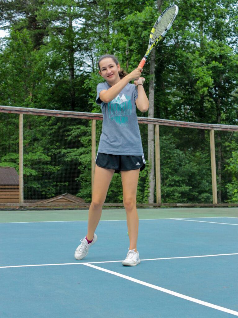 Teen girl swings her tennis racket at Camp Friendship summer tennis program