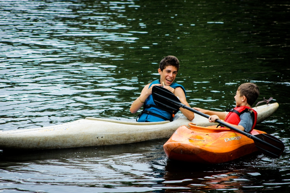 Boy campers kayak in Friendship Lake at coed residential summer camp