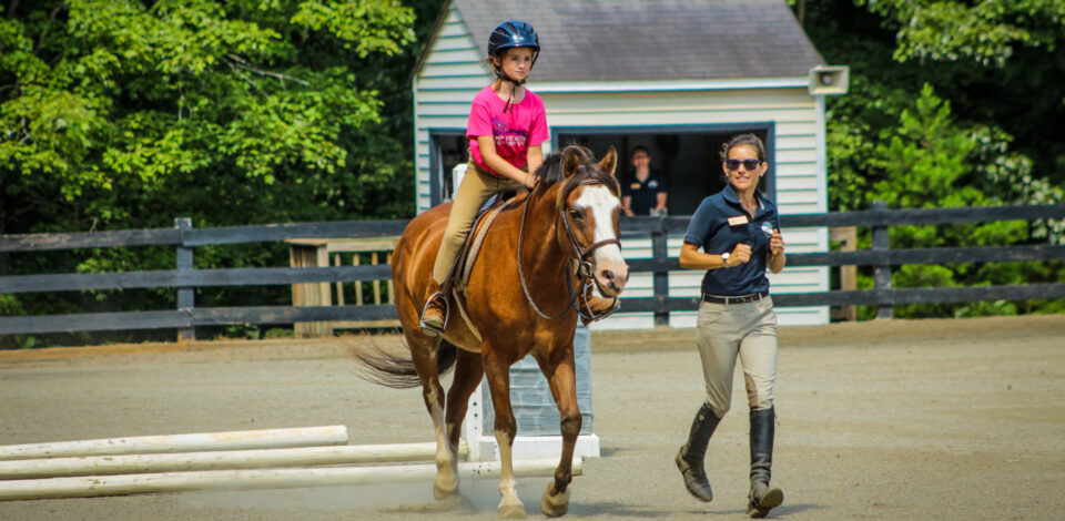 A director helps one of our overnight equestrian campers practice for our horse show.