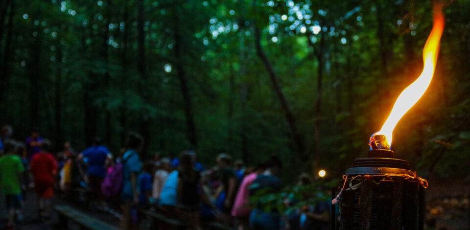 A tiki torch illuminates our overnight camp getting ready for an evening of performances, skits, and songs at campfire.