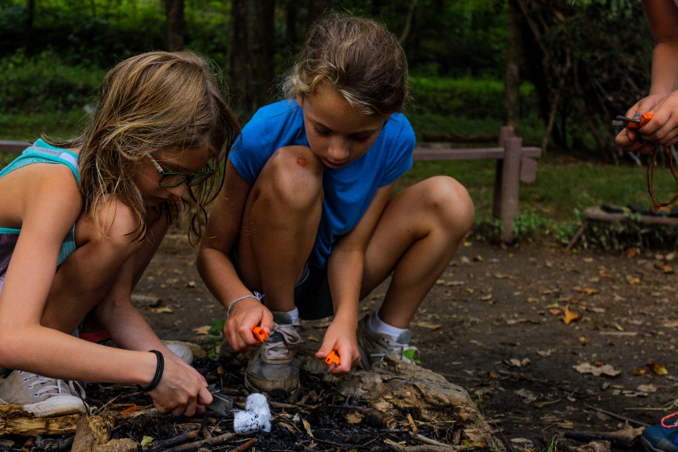 Two girls learning fire building as an activity at Camp Friendship