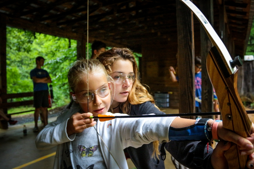 Counselor teaches young girl how to shoot a bow at archery