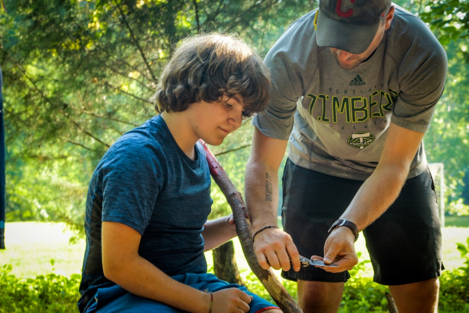 A counselor helps a camper carve his own walking stick for a hike around Virginia trails.