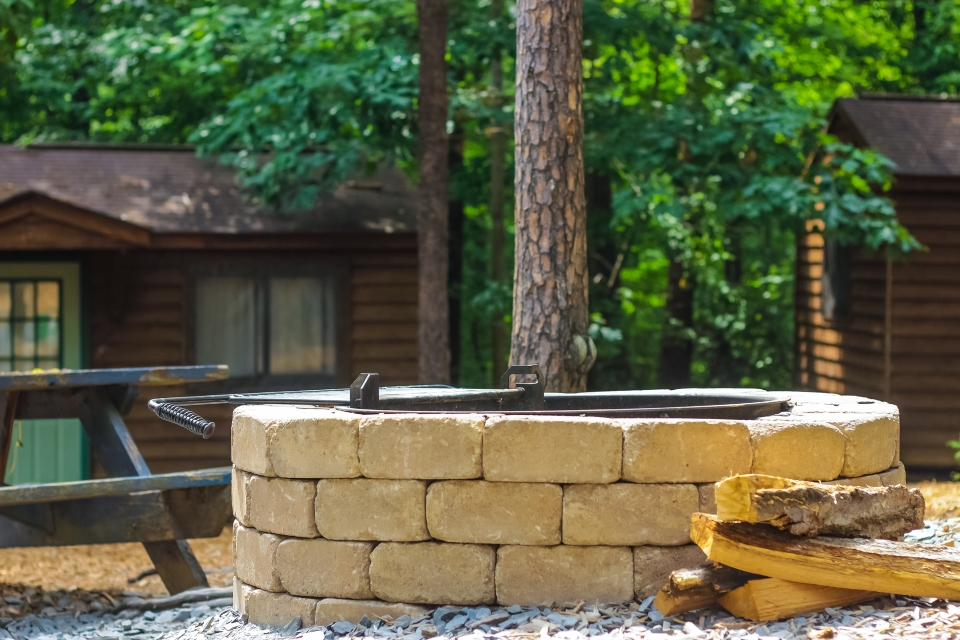 Stone firepit in the center of a few wooden cabins next to a picnic table and some firewood