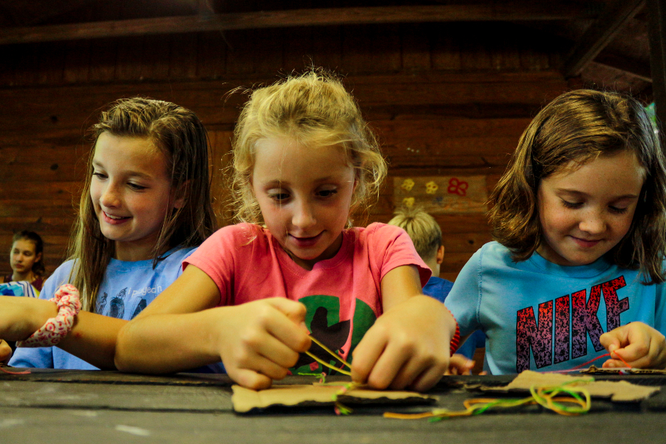 Junior girl overnight campers work on their friendship bracelets to give to their cabin mates.