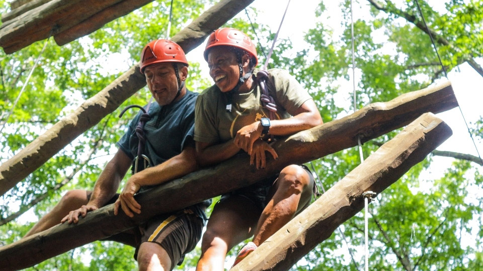 Two adult family campers climbing Jacob's Ladder at Camp Friendship high ropes course