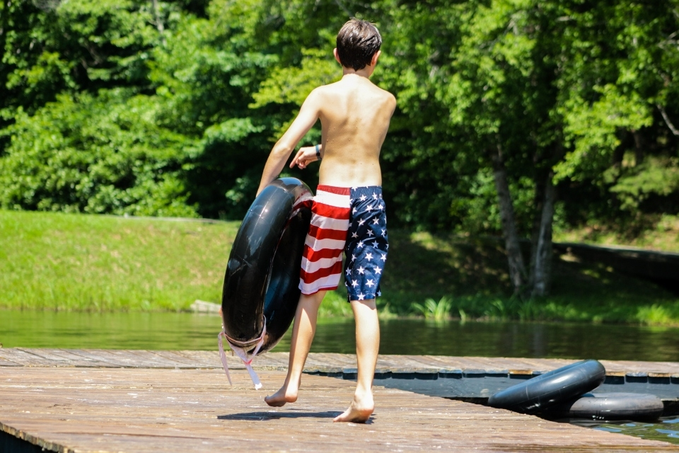 A camper walks across the dock on Friendship Lake with an inner tube ready for fun.