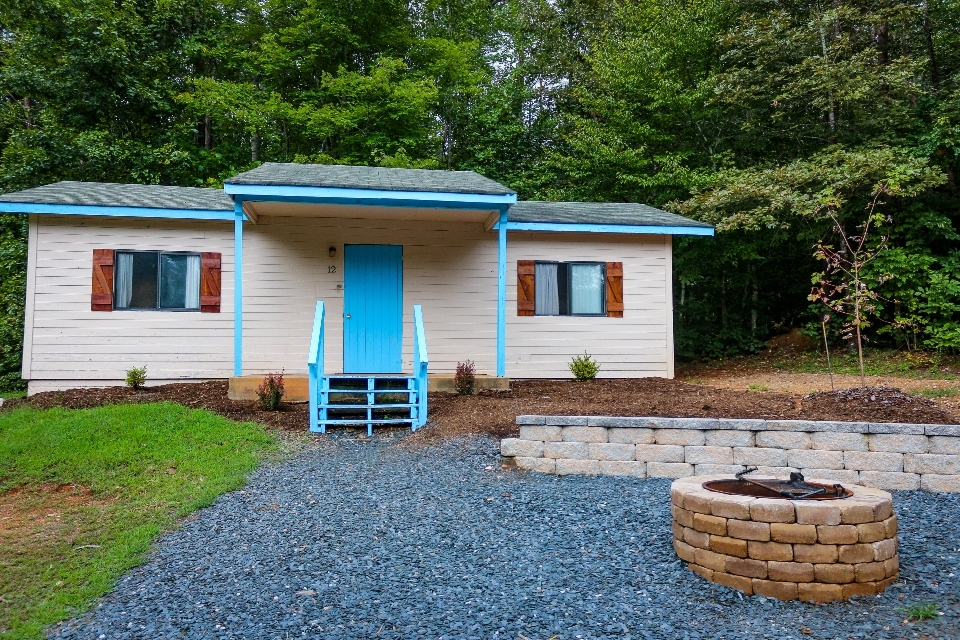 White cabin with blue door and trim at end of gravel path with fire pit