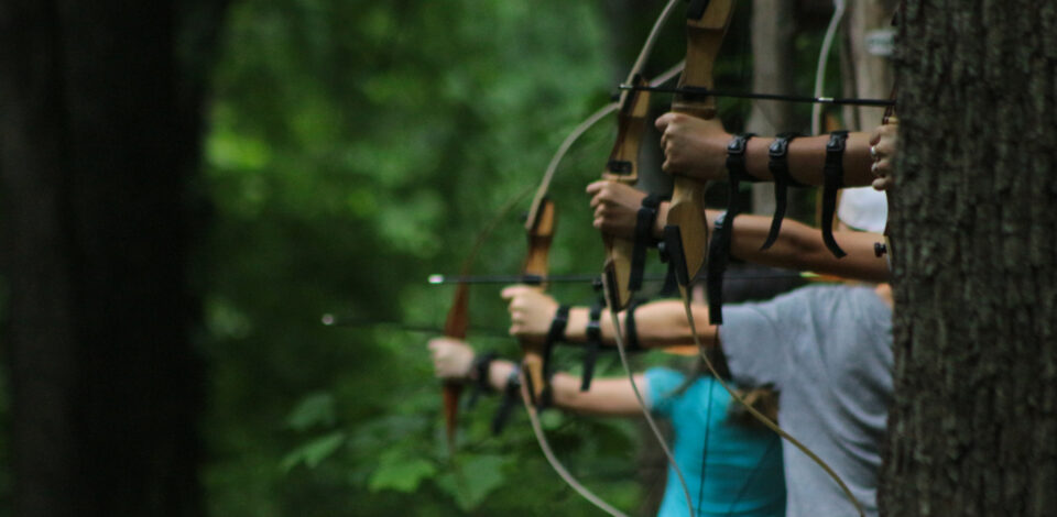A group of teen archers draws their bows for a competition.