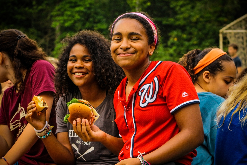 Two of our teen girl campers chow down on hamburgers fresh from our camp grills.
