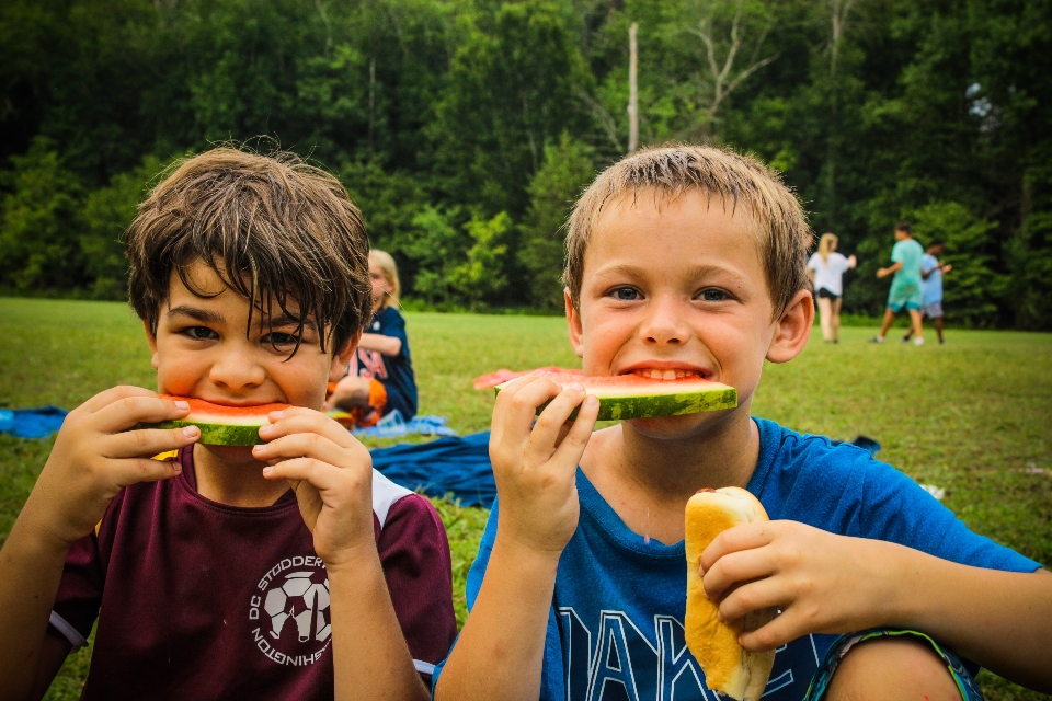 Two junior boys from Camp Friendships overnight camp enjoy watermelon during a break in a soccer game for counselors and kids.