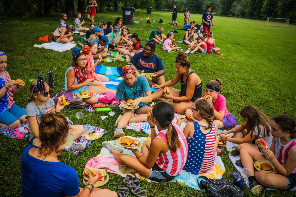 Overnight campers enjoy one of our outdoor cookouts, this one is fourth of July themed and coed junior and teen campers eat together.