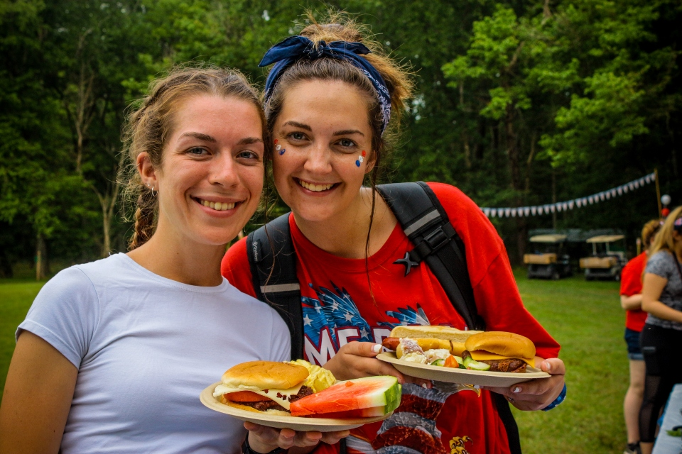 Two counselors, dressed up in red, white, and blue for independence day, enjoy a nice cookout by our coed summer camp archery range.