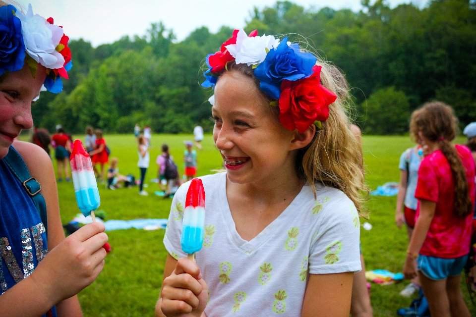 A junior camper celebrates the Fourth of July with a red, white, and blue Popsicle during our cookout on our lower field at Camp.