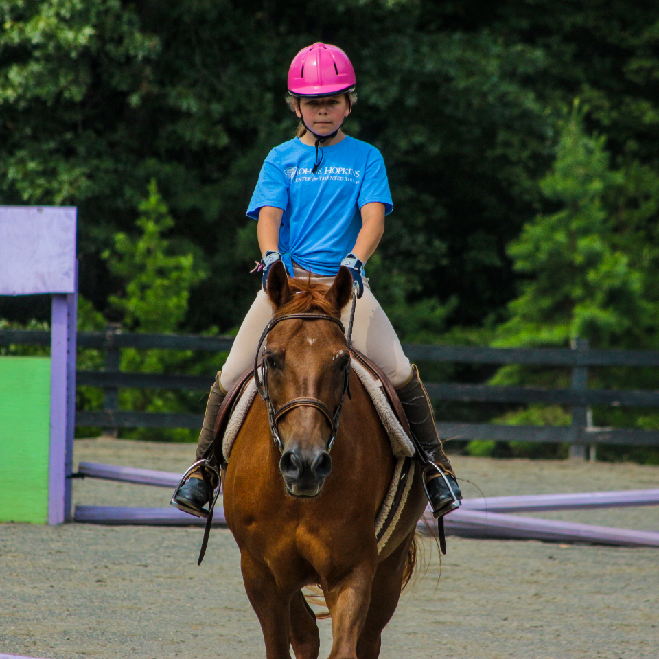 Young girl camper rides her horse in a lesson at an overnight Equestrian summer camp