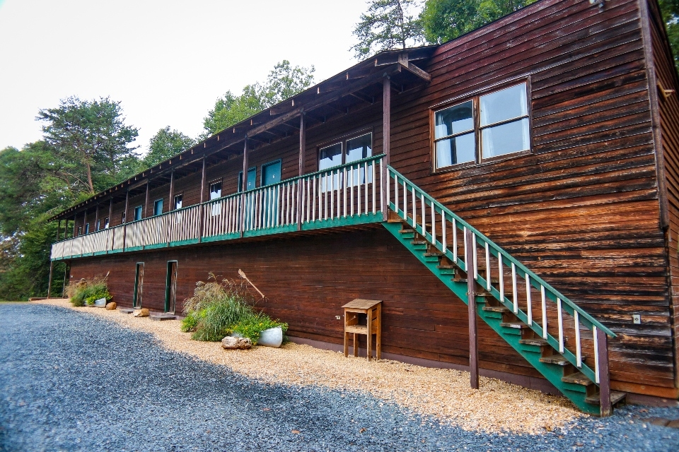 Long wooden two story building with stairs to second floor suites for wedding guest lodging