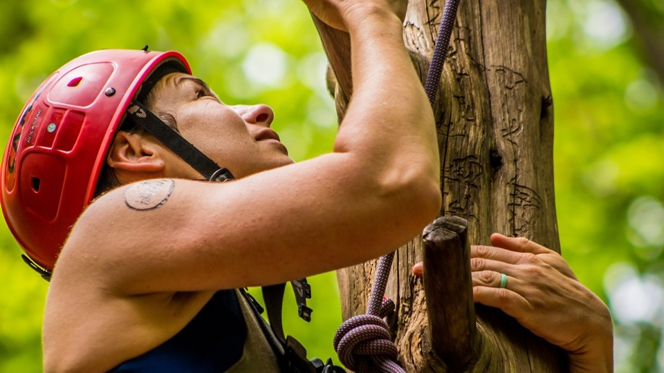 Woman climbing high ropes element at Camp Friendship